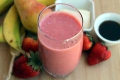 Smoothie rosado hecho con el jarabe de las fresas, de los plátanos, de las peras, del queso de soja y de arce Imagen de archivo