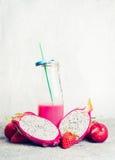 Smoothie rose dans la bouteille avec des ingrédients de fruits tropicaux sur le fond clair, vue de face Photographie stock
