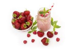 Smoothie rose de fraise et de framboise dans un verre de pot de maçon avec la paille et les baies dispersées Images stock