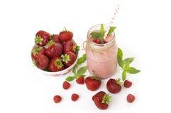 Smoothie rose de fraise et de framboise dans un verre de pot de maçon avec la paille et les baies dispersées Photos stock