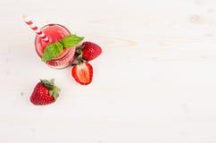 Smoothie rouge fraîchement mélangé de fruit de fraise dans des pots en verre avec la paille, feuille en bon état, baie mûre de co Images stock