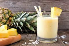 Smoothie sain d'ananas, scène contre le bois Photographie stock