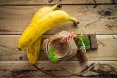 Smoothie sain de banane et de chocolat sur le fond en bois blanc Photo stock