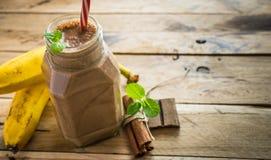 Smoothie sain de banane et de chocolat sur le fond en bois blanc Image libre de droits