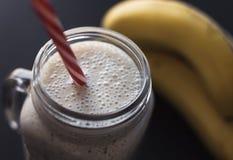 Smoothie sain sur le fond gris La banane, l'avoine, les graines de Chia et le miel se mélangent Photographie stock libre de droits