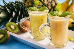 Smoothie sano con el pineaple, la fruta de kiwi y los plátanos imagenes de archivo