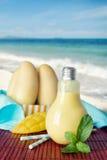 Smoothie sano del mango en tarro de albañil de la bombilla en la playa Fotografía de archivo libre de regalías