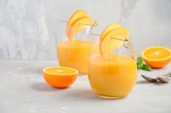Smoothie sano fresco con el caqui, la naranja y el jengibre en fondo concreto gris Foto de archivo libre de regalías