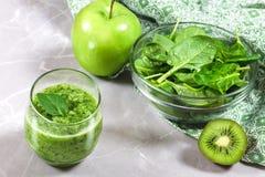 Smoothie sano verde y un cuenco de hojas, de kiwi y de manzana frescos de la espinaca imagen de archivo