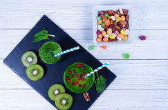 Smoothie spinach and kiwi. In different glasses on a dark stand on a white background and nuts assortment in a white plate. healthy Eating Stock Photo
