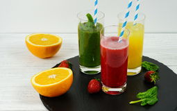 Smoothie spinach and strawberries and orange juice. In a black and white background Stock Photo