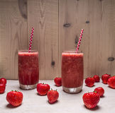 Smoothie of strawberries and berries in glass jars with beautiful tubes on a white wooden table, around expanded fresh strawbe Stock Images