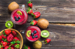 Smoothie with strawberries, kiwi and blueberries in jars Royalty Free Stock Photo