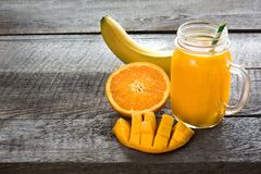 Smoothie with tropical fruits: mango, banana, orange in a glass mason jar on the wooden background. Stock Photos