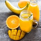 Smoothie with tropical fruits: mango, banana, orange in a glass mason jar on the wooden background. Stock Image
