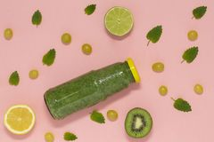 Smoothie verde colorido en botella en el fondo rosado, visión superior imagenes de archivo