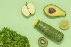 Smoothie verde colorido en botella en el fondo verde, visión superior fotos de archivo