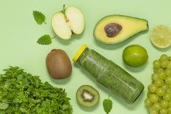 Smoothie verde colorido en botella en el fondo verde, visión superior imagenes de archivo