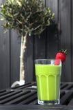 Smoothie verde fresco con la fresa roja Fotografía de archivo