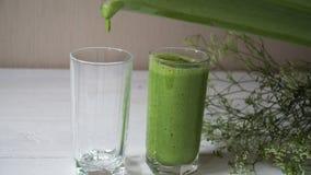 Smoothie verde mezclado con los ingredientes o el cóctel en el fondo blanco, vegano del desayuno con un lugar para su texto almacen de metraje de vídeo