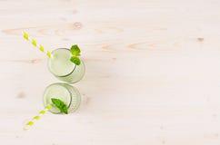 Smoothie verde recientemente mezclado de la fruta de la manzana en los tarros de cristal con la paja, hoja de la menta, visión su Foto de archivo libre de regalías