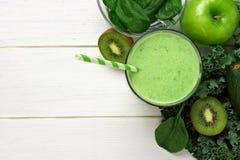 Smoothie verde sobre la visión con los ingredientes contra la madera blanca imagenes de archivo