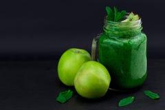 Smoothie vert avec des fruits et légumes sur le fond noir W Photo stock