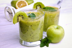 Smoothie vert avec la menthe et les fruits sur le fond en bois Photo stock