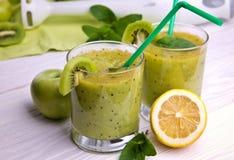 Smoothie vert avec la menthe et les fruits sur le fond en bois Photographie stock