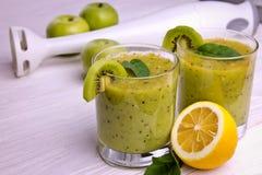 Smoothie vert avec la menthe et les fruits sur le fond en bois Image stock