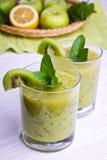 Smoothie vert avec la menthe et les fruits sur le fond en bois Photographie stock libre de droits