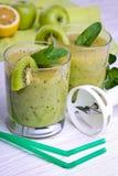 Smoothie vert avec la menthe et les fruits sur le fond en bois Photos stock