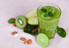 Smoothie vert de kiwi Un cocktail avec les pommes, la chaux, la menthe et le kiwi sur un fond clair de table Produits à base de f Photo libre de droits