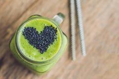 Smoothie vert frais avec la banane et les épinards avec le coeur des graines de sésame Amour pour un concept cru sain de nourritu Photo libre de droits