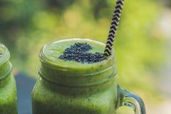 Smoothie vert frais avec la banane et les épinards avec le coeur des graines de sésame Amour pour un concept cru sain de nourritu Photographie stock libre de droits