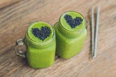 Smoothie vert frais avec la banane et les épinards avec le coeur des graines de sésame Amour pour un concept cru sain de nourritu Image stock