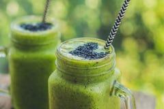 Smoothie vert frais avec la banane et les épinards avec le coeur des graines de sésame Amour pour un concept cru sain de nourritu Image libre de droits