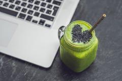Smoothie vert frais avec la banane et les épinards avec le coeur du sesam Image stock
