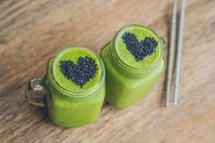 Smoothie vert frais avec la banane et les épinards avec le coeur du sesam Photographie stock