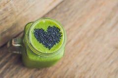 Smoothie vert frais avec la banane et les épinards avec le coeur du sesam Images libres de droits