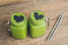 Smoothie vert frais avec la banane et les épinards avec le coeur du sesam Images stock