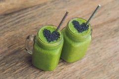 Smoothie vert frais avec la banane et les épinards avec le coeur du sesam Photos stock
