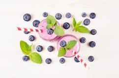 Smoothie violet fraîchement mélangé de fruit de myrtille dans des pots en verre avec la paille, feuilles en bon état, baies, vue  Photos stock