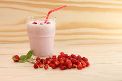Smoothie from wild strawberries in a glass and wild strawberries Stock Images