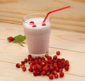 Smoothie from wild strawberries in a glass and wild strawberries Stock Photos
