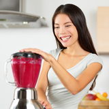 Smoothie woman blending healthy beet - fruit juice. Asian young adult using home appliance kitchen blender to make vegan organic vegetable smoothie using raw stock photography