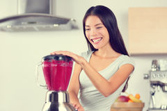 Smoothie woman making fruit smoothies. With blender. Healthy eating lifestyle concept portrait of beautiful young woman preparing drink blending strawberries royalty free stock photography