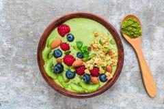 Smoothiebunke som göras av grönt te för matcha med nya bär, muttrar, frö med en sked för sund strikt vegetarianfrukost arkivbilder