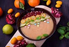 Smoothiebunke som garneras med kumquats, granatäpplet, limefrukt och mintkaramellen arkivbild