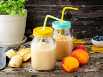 Smoothien för bananpersikanektarinen skorrar itu, milkshaen för ny frukt arkivfoto